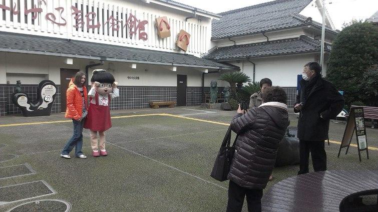 Марина Гуща вместе с персонажем Нэко Мусумэ на фоне здания музея Мидзуки  Сигэру  © фото: Анастасия Жернакова